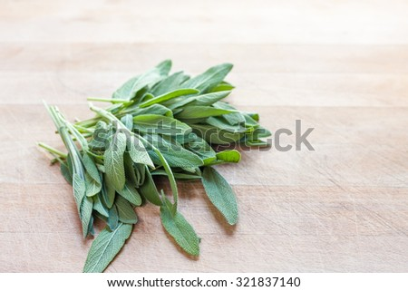 A bunch of fresh sage leaves on a wooden surface - stock photo