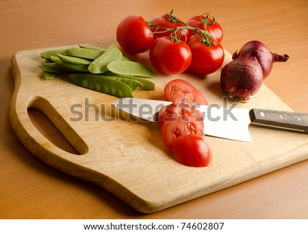 a bunch of fresh vegetables on a wooden cutting board - stock photo
