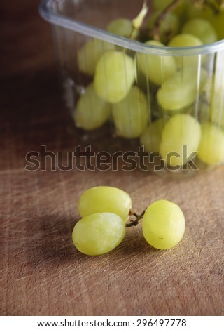 A bunch of fresh white grapes on a wooden board - stock photo