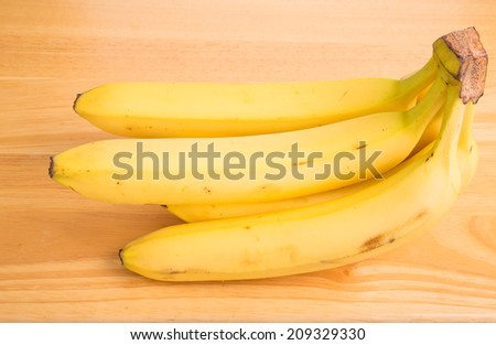 A bunch of fresh yellow bananas on a wood table