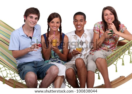 A bunch of friends enjoying cocktails on a hammock. - stock photo