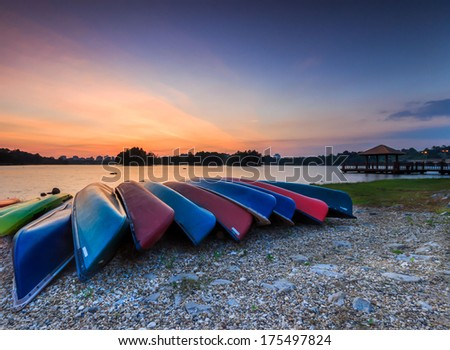 A bunch of kayaks stranded with a sunset view. - stock photo