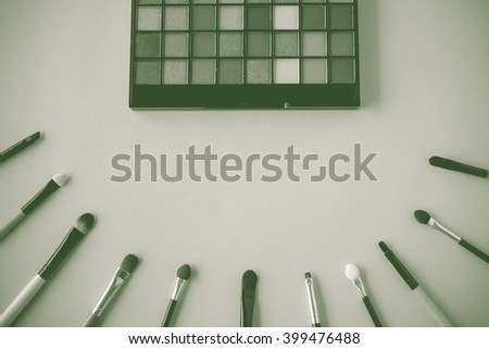 A bunch of make-up brushes and Cosmetics, Set of makeup brush and contour palette, Women accessories. (Vintage with green toned Style Color) - stock photo