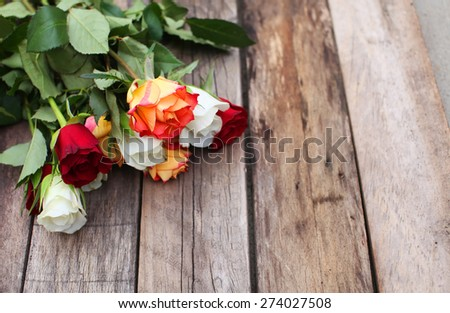 A bunch of mixed colors roses over wooden table background