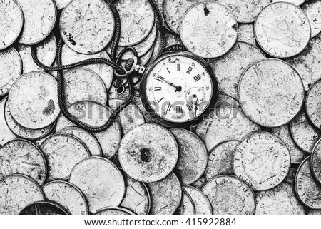 A bunch of old coins with a broken pocket watch on top, monochromatic top view. - stock photo