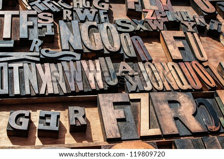 A bunch of old vintage wooden block printing press letters. - stock photo