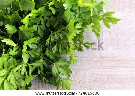A bunch of parsley on a wooden background with space for text.