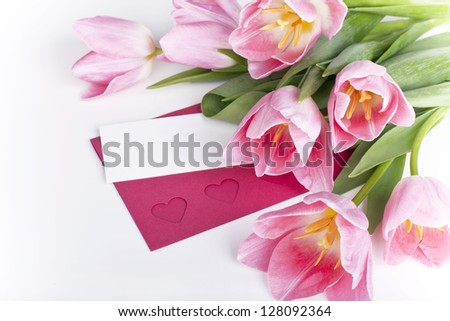 A bunch of pink tulips with a blank card for greetings - stock photo