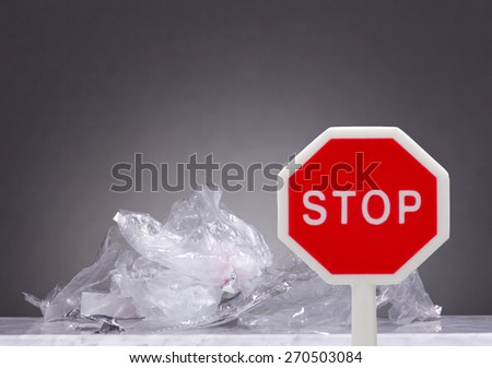 A bunch of plastic garbage lies on a marble table.In front of the trash is a stop sign. Methaphor for stopping  producing trash . Gray Background.  - stock photo