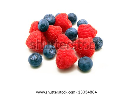 A bunch of plump delicious raspberries and blueberries isolated on white