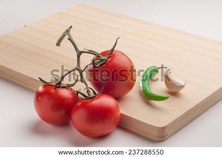 A bunch of tomatoes, green chili and a clove of garlic arranged on a wooden chopping board. - stock photo