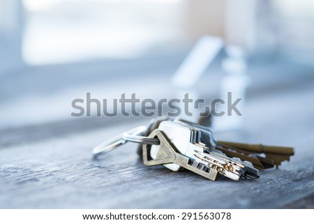 A bunch of vintage keys with metal house on the wooden table - stock photo