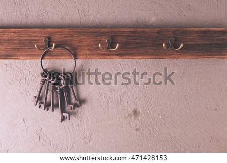 A bunch of vintage metal keys on ring hanging on hooks wooden hangers