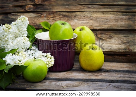a bunch of white  lilac and green apples on old wooden background