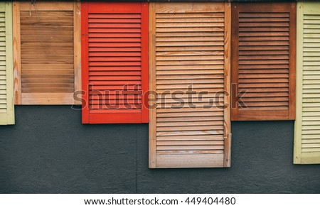 A bunch of wooden window shutters pattern on grey wall. Restaurant cafe warehouse decor. Naked worn wooden and plain painted shutters. Hipster wallpaper.  - stock photo