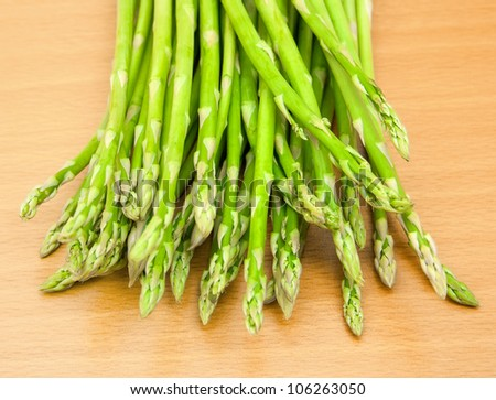 A bunch of young fresh asparagus on the table - stock photo