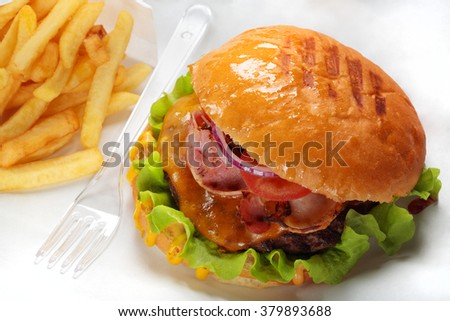 A burger, fries and fork on paper - stock photo