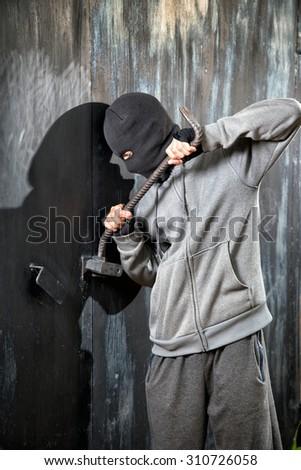 a burglar breaking open of a padlock metal door - stock photo