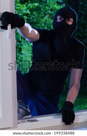A burglar enters the house through the window - stock photo