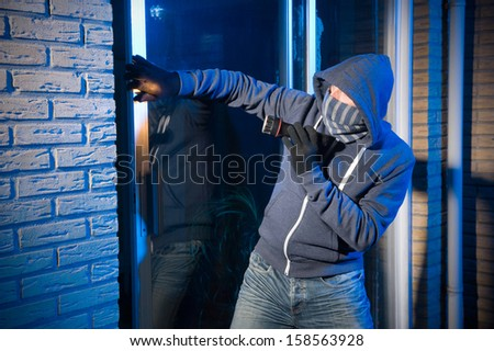 A burglar is opening the backdoor of a house - stock photo