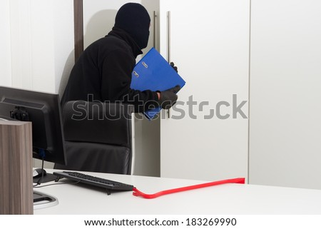 A burglar is robbing knowledge from a company - stock photo