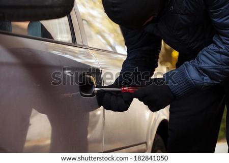 A burglar opening car's door by breaking in - stock photo