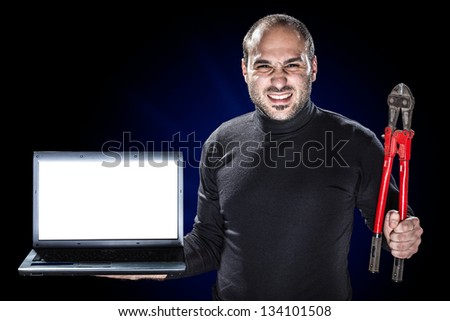 a burglar or a cyber criminal holding a laptop with blank monitor and big red shears - stock photo