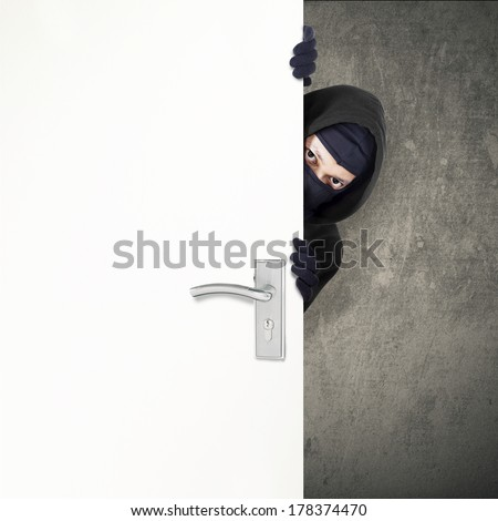 A burglar sneaking in a open house door during a break and enter past security locks and alarms, - stock photo