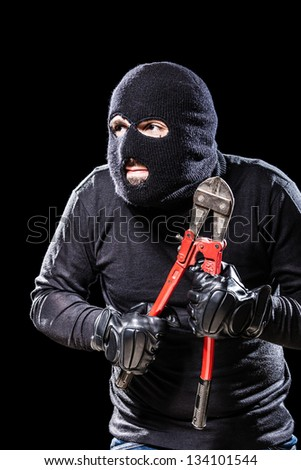 a burglar wearing a balaclava holding huge wire cutters over black background