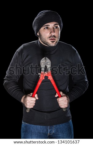 a burglar wearing black clothes holding huge wire cutters over black background