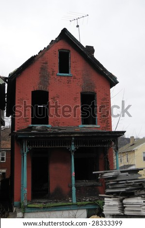A burned brick house stands abandoned in downtown Braddock, Pennsylvania, a steel town in decline - stock photo