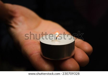 a burning candle in his hand - stock photo