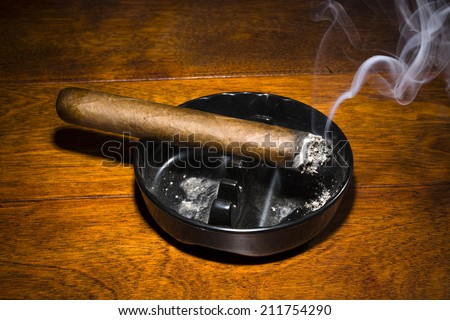 A burning cigar in a classic black ashtray streaming smoking in a dark, moody setting. The smoke is real, straight from the cigar and not put in later during post processing. - stock photo