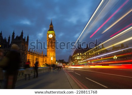 A bus speeding past tourists admiring Big ben and Houses of Parliament on Westminster Bridge in London, England. - stock photo