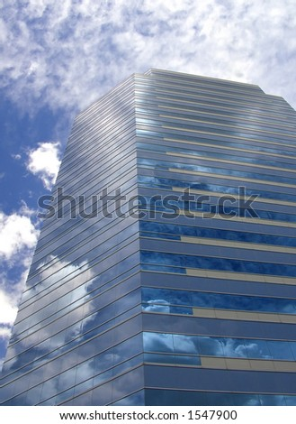 A business building reflects the sky.