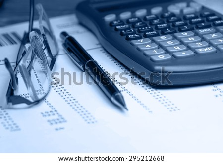 A business calculation lying on a desk with hourgkass and pair of reading glasses. Blue toned image - stock photo