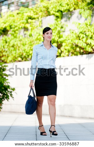 A business executive walking in a green part of the city