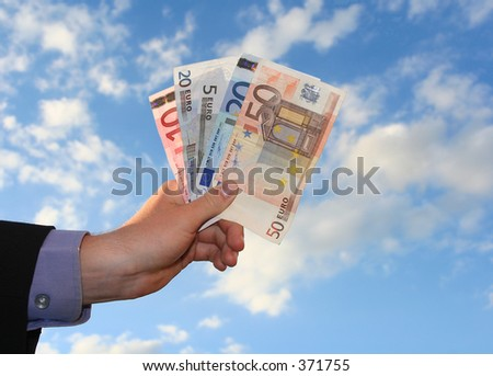 a business hand holding money in front of cloudy sky