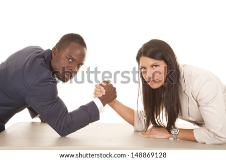 A business man and woman arm wrestling with serious expressions on their faces.