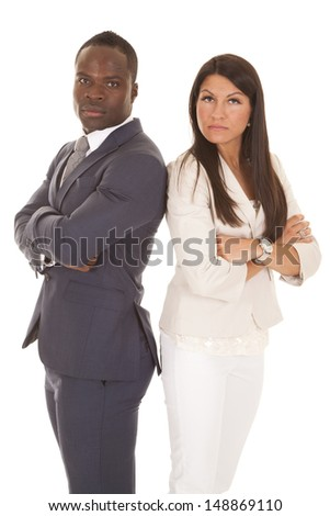 A business man and woman standing back to back with serious expressions on their faces. - stock photo