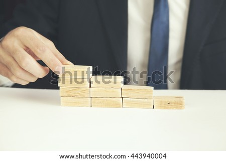 a business man build a blocks wood game - stock photo