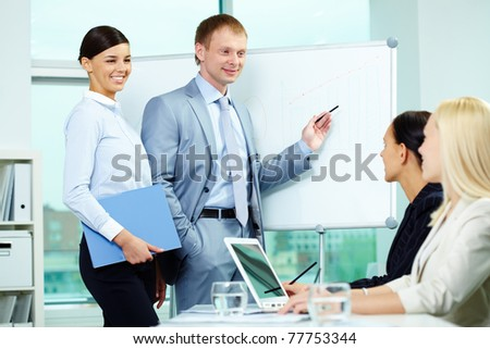 A business man explaining something on a whiteboard with pretty woman near by