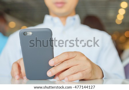 A business man hand touch a Smart Phone on his hand in Restaurant with Bokeh light, Technology background concept