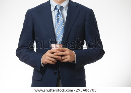 A business man holding a cup of coffee