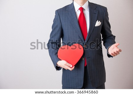 A business man holding a heart shaping note.