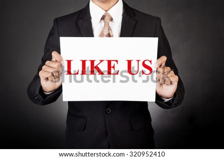 A business man holding a paper in front of his face:like us concept - stock photo