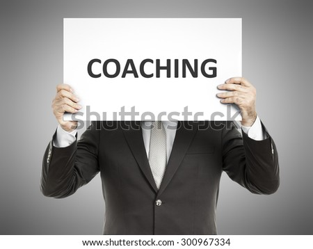 A business man holding a paper in front of his face with the message coaching - stock photo