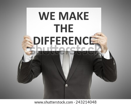 A business man holding a paper in front of his face with the message we make the difference - stock photo