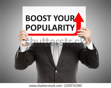A business man holding a paper in front of his face with the text boost your popularity - stock photo