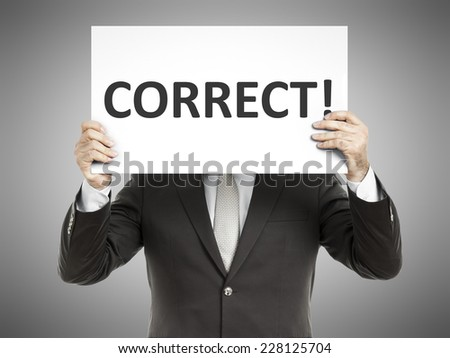 A business man holding a paper in front of his face with the text correct - stock photo